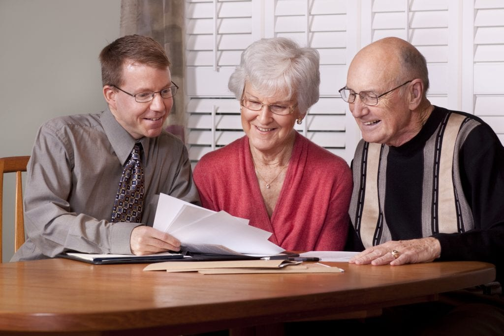 Financial advisor presenting documents to an elderly couple