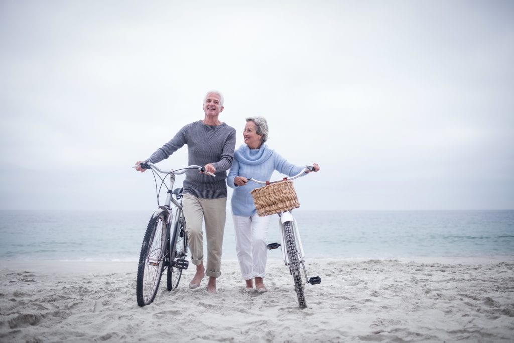 Senior couple on a beach with their bikes
